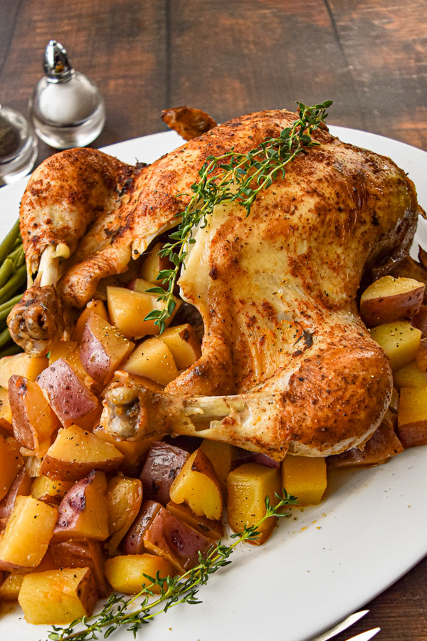 Low Fodmap instant pot whole chicken with potatoes and green beans on a white platter on a brown wood background