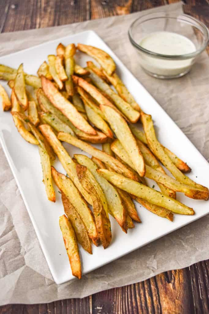 low fodmap french fries on a white, rectangular plate next to a bowl of ranch dressing on parchment paper