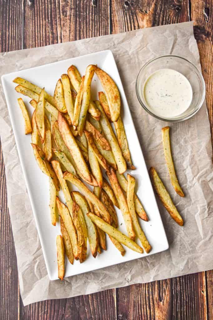 low fodmap French fries on a white, rectangular plate with a bowl of ranch dressing