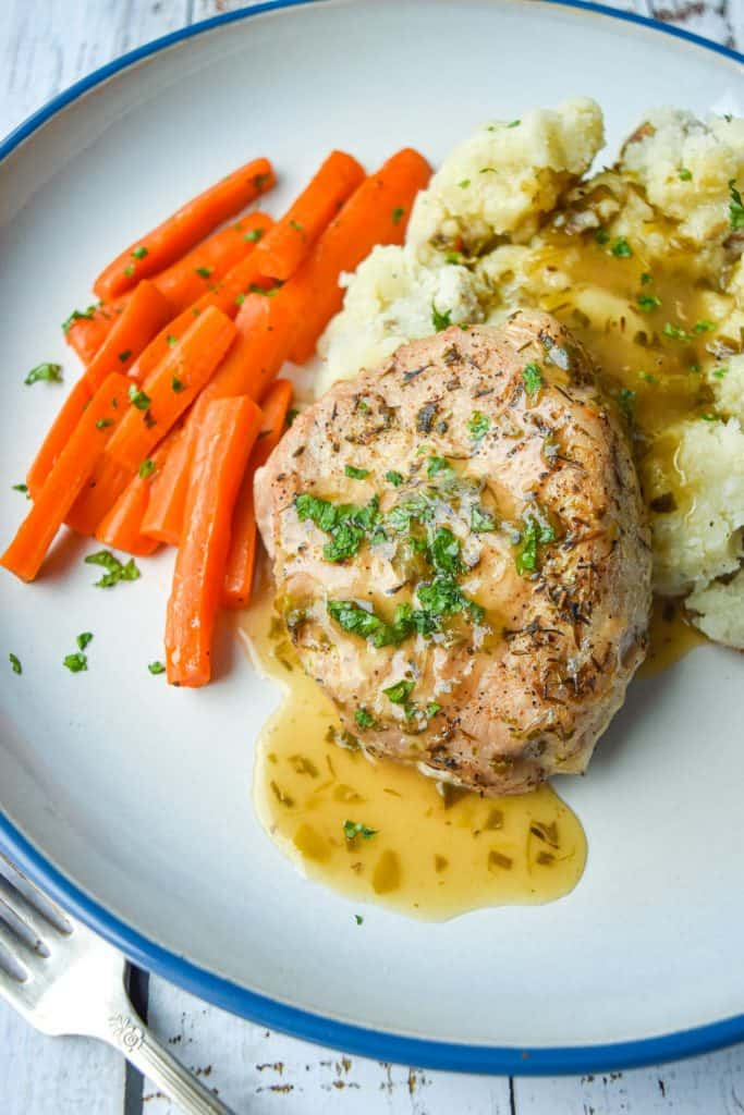 close up shot of a low fodmap pork chop, mashed potatoes, carrots and gravy on a blue rimmed white plate
