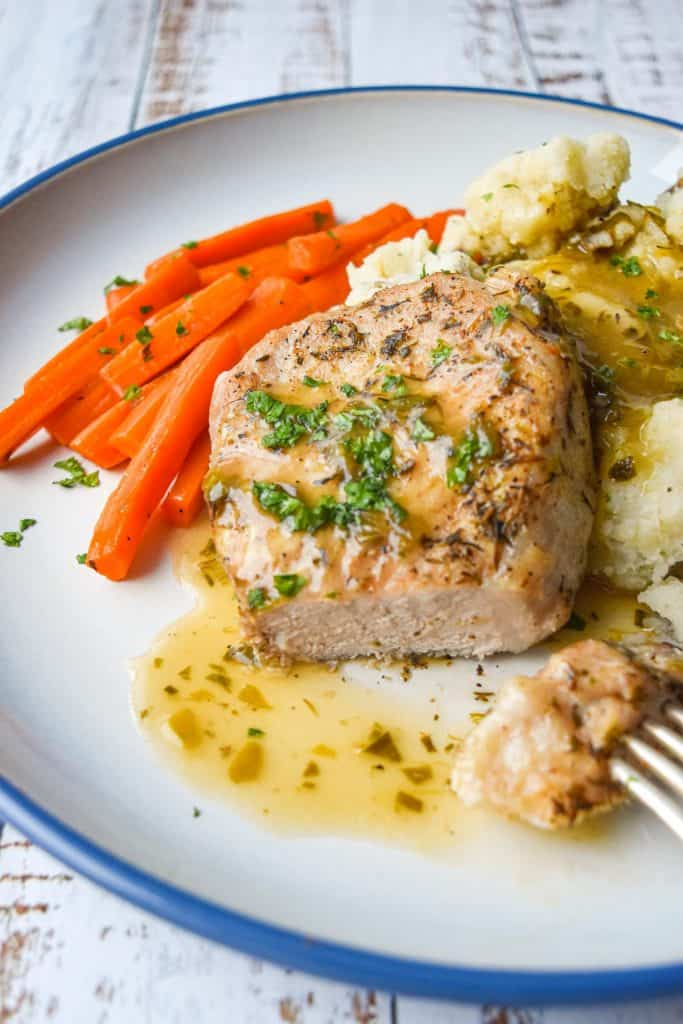 a plate with a cut low fodmap pork chop, carrots, mashed potatoes and gravy
