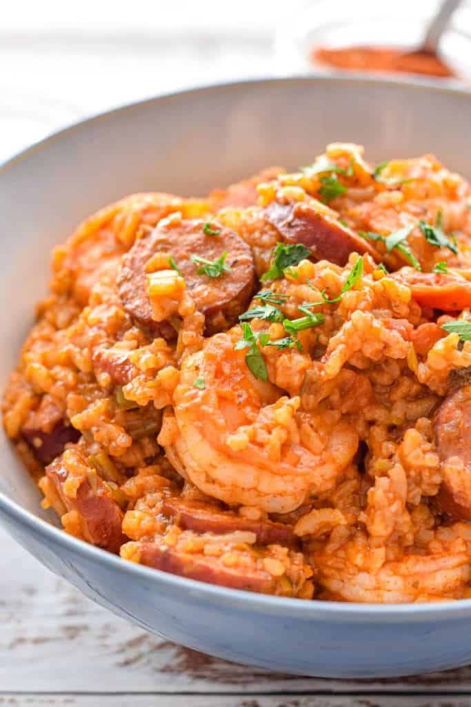 low fodmap instant pot jambalaya in a blue and white bowl garnished with chopped parsley