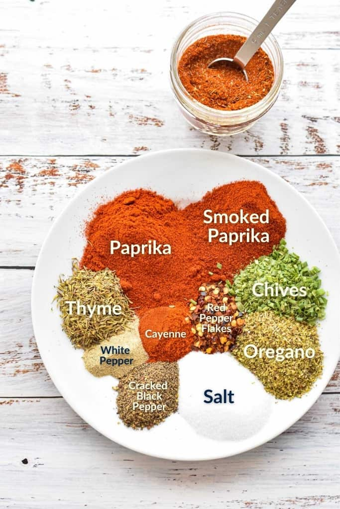 diagram of low fodmap cajun seasoning mix ingredients on a white plate including paprika, smoked paprika, chives, oregano, thyme, salt, black pepper, white pepper, cayenne pepper, and red pepper flakes