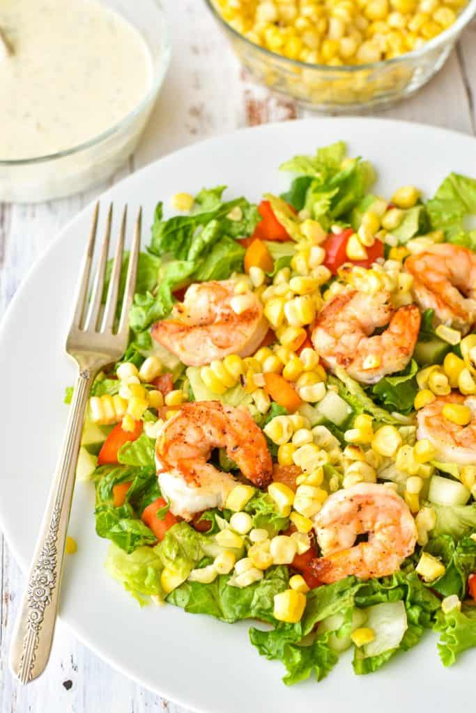 side angle shot of detox salad containing lettuce, bell pepper, cucumber, corn and shrimp on a white plate with a fork with bowls of corn and ranch dressing behind