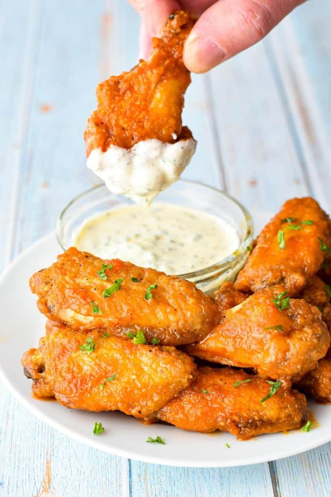 a chicken wing drumette dipped in ranch dressing over a plate of buffalo wings