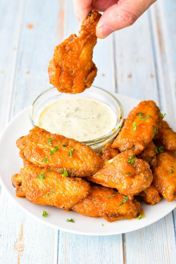 a hand holding a low fodmap buffalo wing over a small bowl of ranch dressing