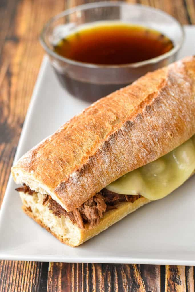 a low fodmap beef dip on a white rectangular plate with a bowl of au jus
