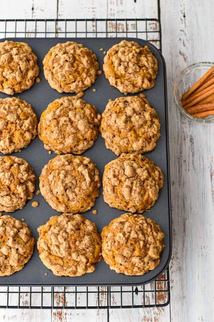 overhead shot of a muffin pan full of freshly baked pumpkin zucchini muffins next to a bowl of cinnamon sticks