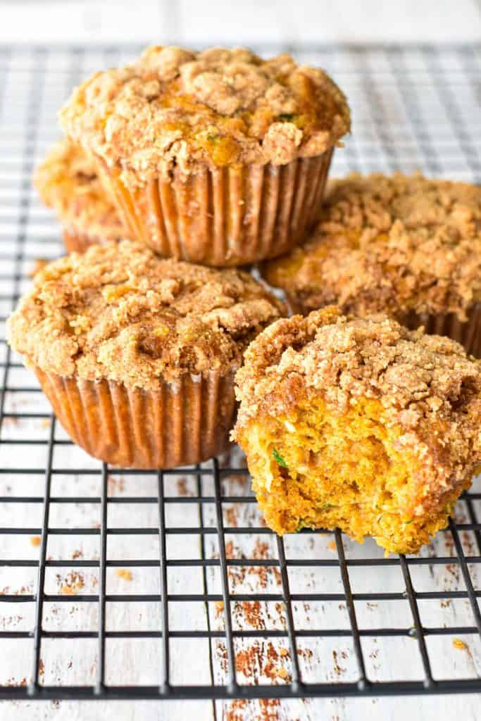 a stack of low fodmap pumpkin zucchini muffins with a muffin with a bite taken out of it on a cooling rack