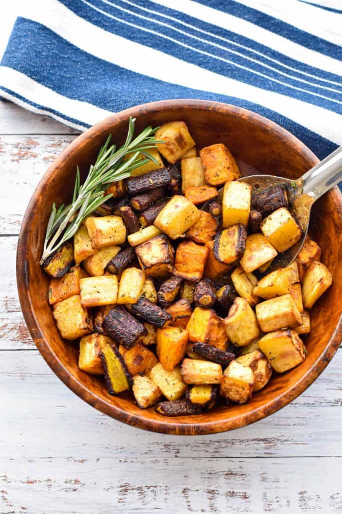 low fodmap air fryer root vegetables in a wooden bowl with a spoon and spring of rosemary
