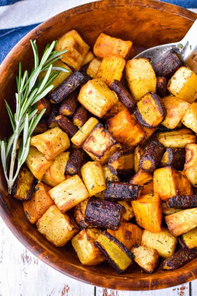 close-up shot of a  bowl low fodmap air fryer root vegetables garnished with a rosemary sprig