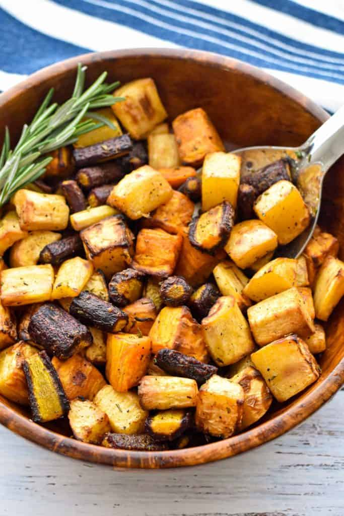 low fodmap root vegetables in a wooden bowl with a spoon on a painted white background